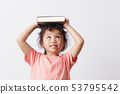 Asian little girl holding a book on head  53795542
