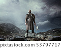 Viking with axe standing in rocky mountains 53797717