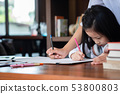 cute girl smiled and sitdown to drawing a book in 53800803