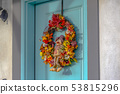A colorful autumn wreath with small scarecrow 53815296