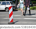 Young couple walk on the zebra crossing 53816430