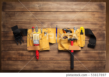 instruments in tool belt at wooden table 53817897