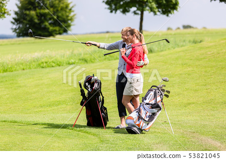 Woman looking at his boyfriend standing on golf course 53821045