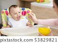 Mother giving healthy food to her adorable baby child 53829821