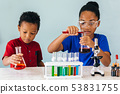 Two African American mixed kids testing chemistry lab experiment 53831755