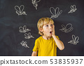 The boy is bitten by mosquitoes on a dark background. On the blackboard with chalk painted 53835937