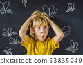 The boy is bitten by mosquitoes on a dark background. On the blackboard with chalk painted 53835949