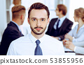 Businessman headshot against a group of business people at a meeting or negotiation in office 53855956