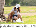 Asian lifestyle woman playing with golden retrieve 53858379