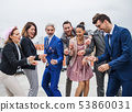 A group of joyful businesspeople having a party outdoors on roof terrace in city. 53860031