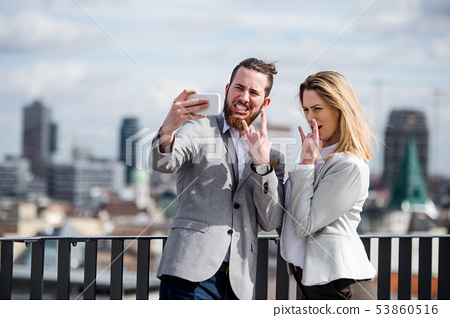 Two young business people with smartphone standing on a terrace, taking selfie. 53860516