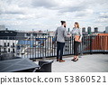Two young business people standing on a terrace outside office, shaking hands. 53860521