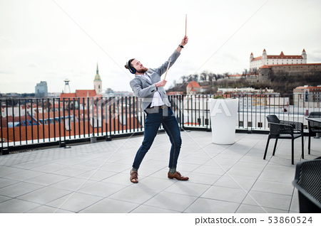 A young businessman with headphones standing on a terrace, having fun. 53860524