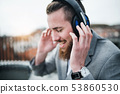 A young businessman with headphones on a terrace, listening to music. 53860530