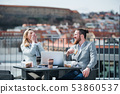 Two young business people sitting on a terrace outside office, having lunch break. 53860537