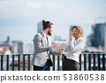 Two young business people with tablet standing on a terrace outside office, working. 53860538