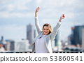 A young businesswoman standing on a terrace, expressing excitement. 53860541