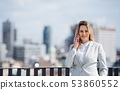 A young businesswoman with smartphone standing on a terrace, working. 53860552