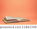 Open old book on a beautiful coral orange 53862399