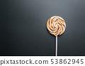 Caramel lollipop on pink 53862945