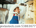 HVAC technician working on a capacitor part for condensing unit 53863677