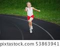 happy little girl running on the stadium 53863941