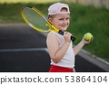 happy girl plays tennis on court outdoors 53864104