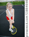 happy girl plays tennis on court outdoors 53864698