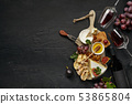 Two glasses of red wine and cheese plate with fruit on the black stone 53865804