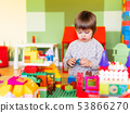 Little boy playing in kidsroom with constructor 53866270