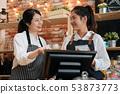 barista working together behind bar counter 53873773