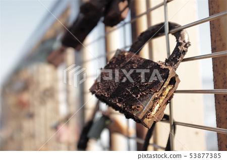 生鏽的鎖頭掛在鐵絲網牆上 53877385