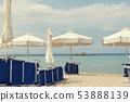 White solar umbrellas and blue beach chairs  53888139