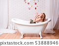 Woman in bath having fun with flowers. Beautiful young blonde woman enjoying pleasant bath, looking 53888946