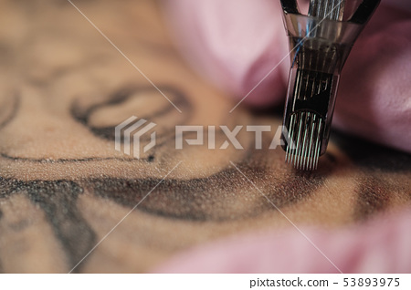 Close-up of a tattoo needle. The process of the tattoo master. Pink women's protective gloves. 53893975