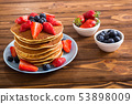 Tasty pancakes with blueberry and strawberry 53898009