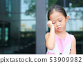 Serious little girl with posture her hand on head. 53909982