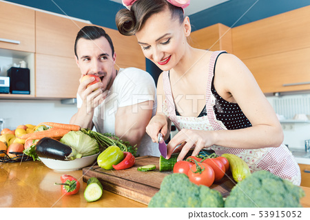 Rather lazy man Is watching his wife preparing the food 53915052