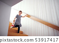 A small child with a soft toy walking down the stairs. 53917417
