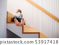A rear view of small girl lying down on staircase. Copy space. 53917418