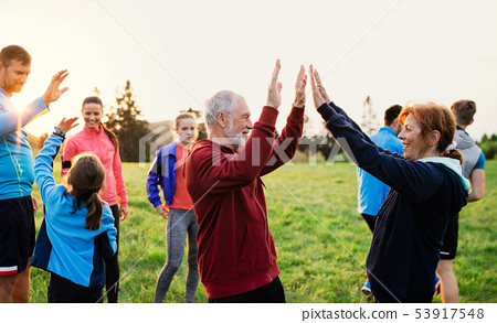 Large group of fit and active people resting after doing exercise in nature. 53917548