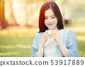 Girl teen holding mug to drinking hot tea  53917889