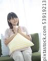 一個女人坐在沙發上,有一杯咖啡 53919213