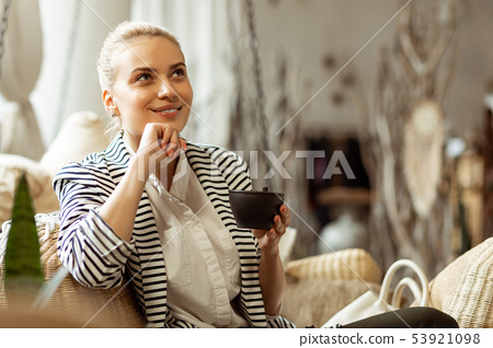 Thoughtful good-looking woman with soft smile holding black cup of tea 53921098
