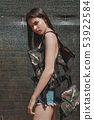 Adorable woman, fashionable model, with long, brunette hair in camouflage vest 53922584