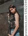 Adorable woman, fashionable model, with long, brunette hair in camouflage vest 53922594