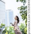 站立在汉城市中心的年轻女性模型与摩天大楼在背景中 53926840