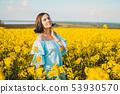 Portrait of pretty woman in blue dress posing in rapeseed yellow flowers field 53930570