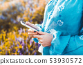 Hands of woman using smartphone in flowers field. Technology concept. 53930572