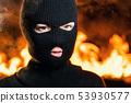 Portrait of female protesting activist in balaclava against burning barricades 53930577